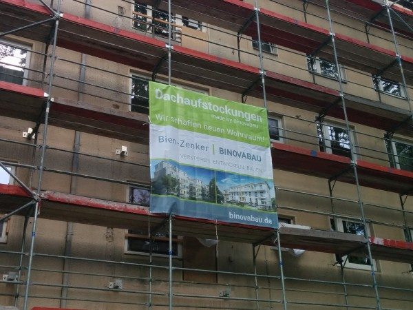 Plakat am Baugerüst: Dachaufstockungen Bien-Zenker | Binovabau